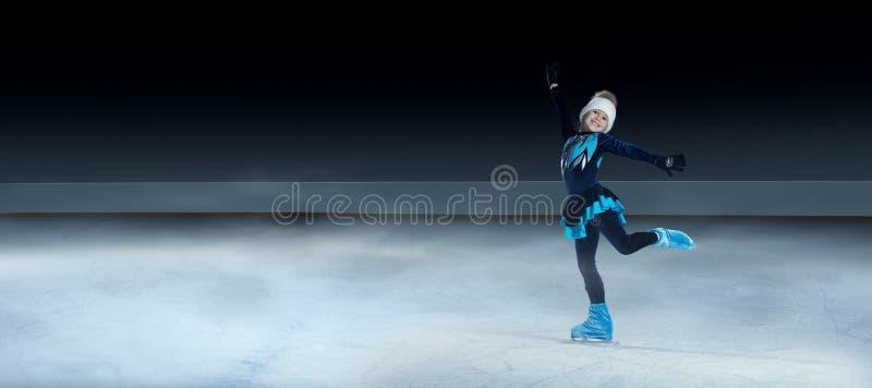 Child  figure skater on dark ice arena background stock photo