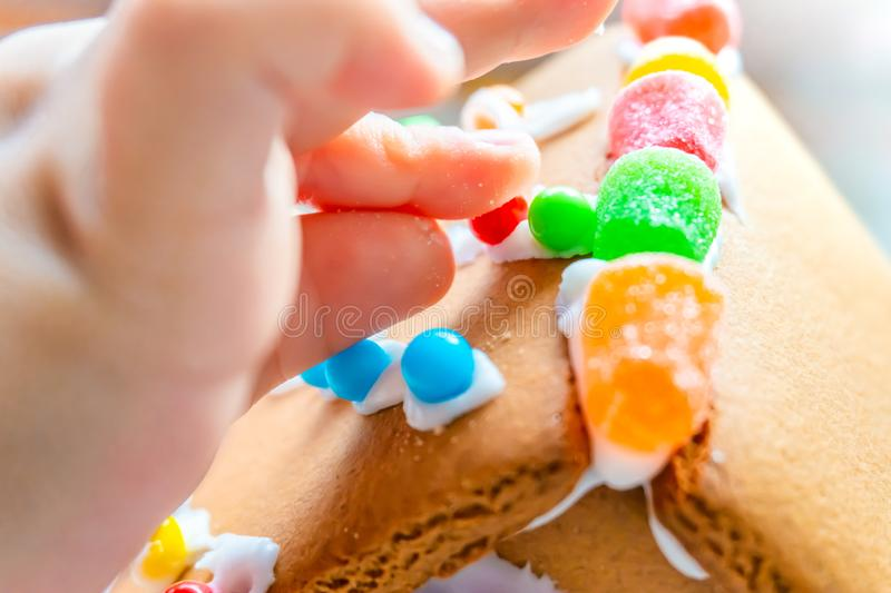 Child fingers placing candy balls and gummies on a gingerbread house roof with icing sugar as a creative and classic, seasonal stock photography