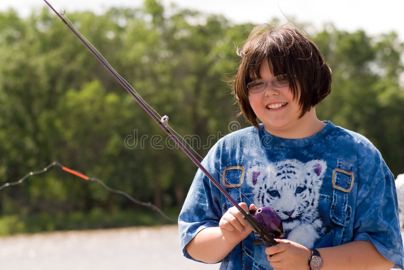 Child Fishing. A young girl fishing on a warm summer day royalty free stock photo