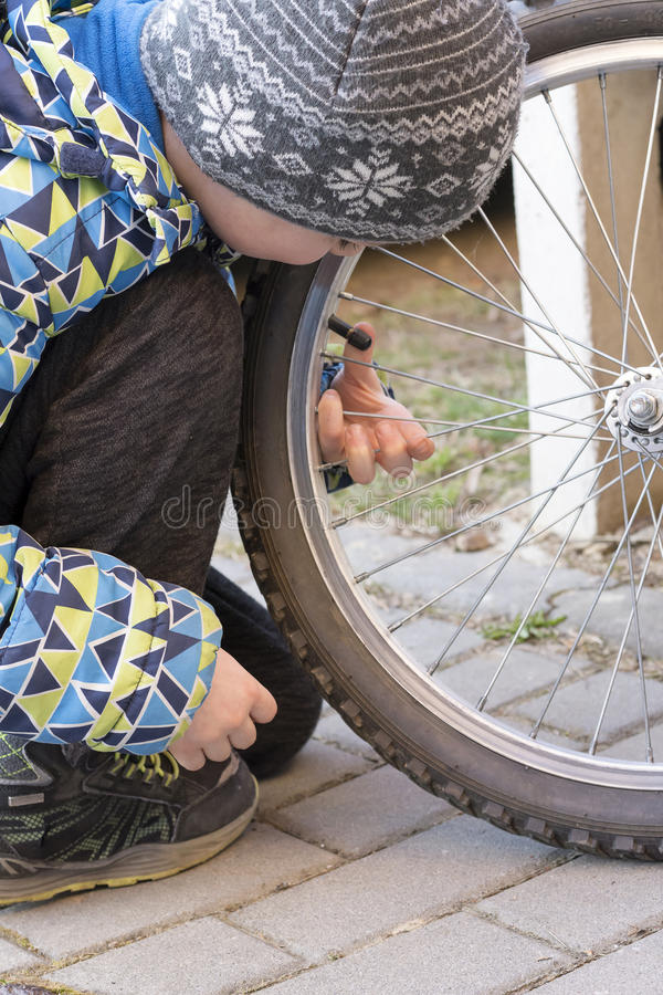 Child fixing bike or bicycle. Child checking the tire on a bicycle or bike royalty free stock photo