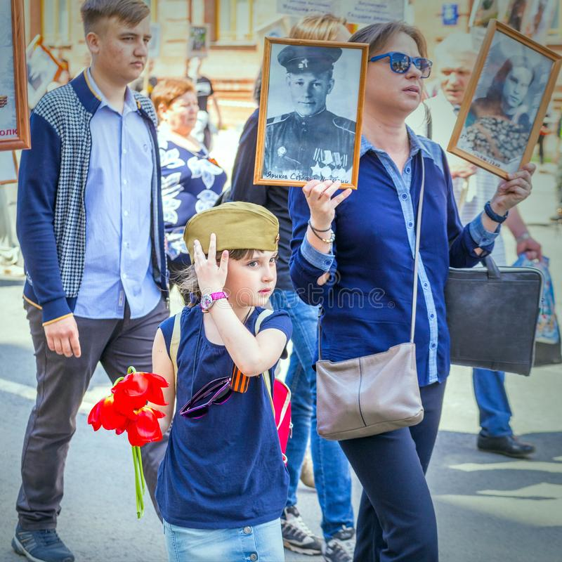 A child with flowers on the action `Immortal Regiment. Russia, Samara, May 9, 2018: A child with flowers on the action `Immortal Regiment stock photography