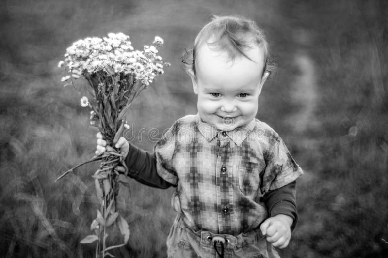 Child with flowers in nature. Joyful face expression, monochrome converted from raw file stock photo