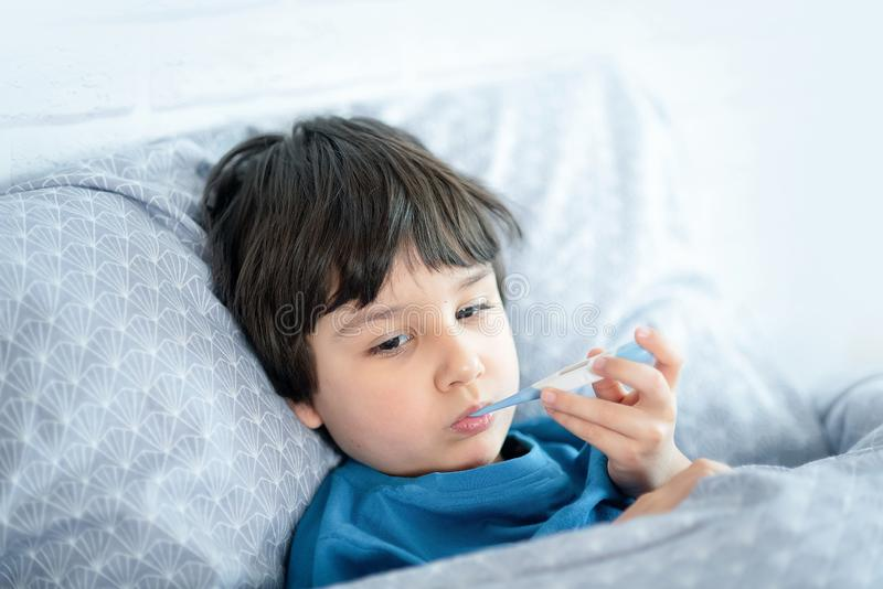 Child flu sick, boy with medical thermometer in mouth, health illness. Kid with cold rhinitis, get cold. Fever, temperature, bed, caucasian, little, young stock photos