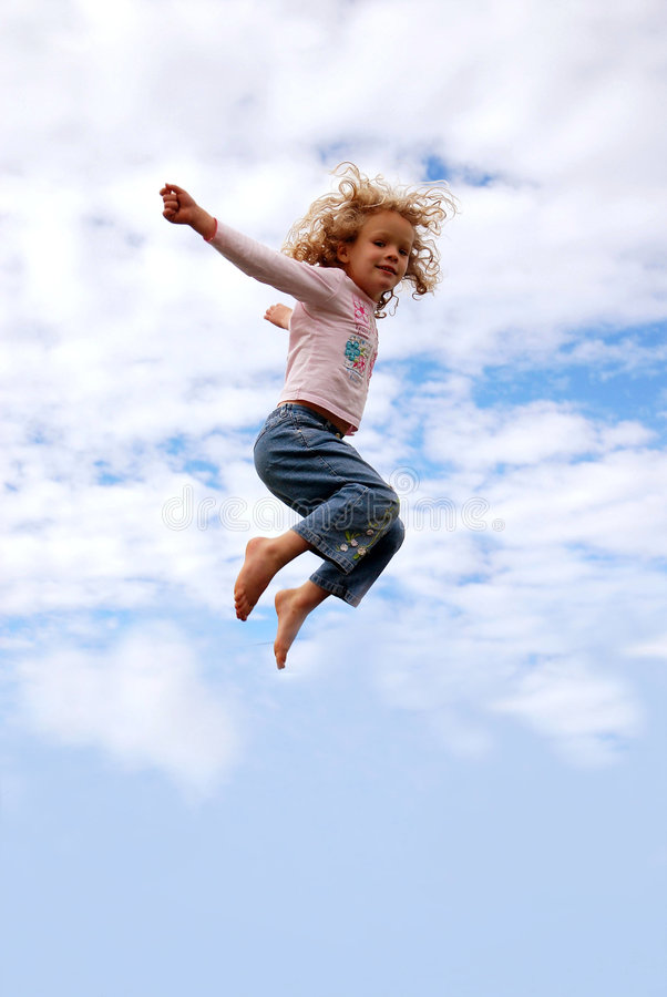 Child flying. A cute little jumping caucasian girl child with happy smiling facial expression flying high up in the sky after jumping on a trampoline royalty free stock images