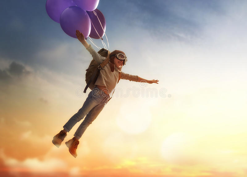 Child flying on balloons stock image