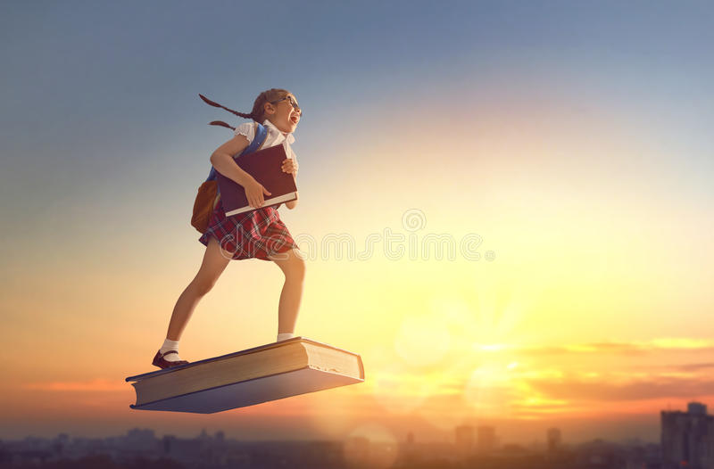 Child flying on the book. Back to school! Happy cute industrious child flying on the book on background of sunset urban landscape. Concept of education and royalty free stock image