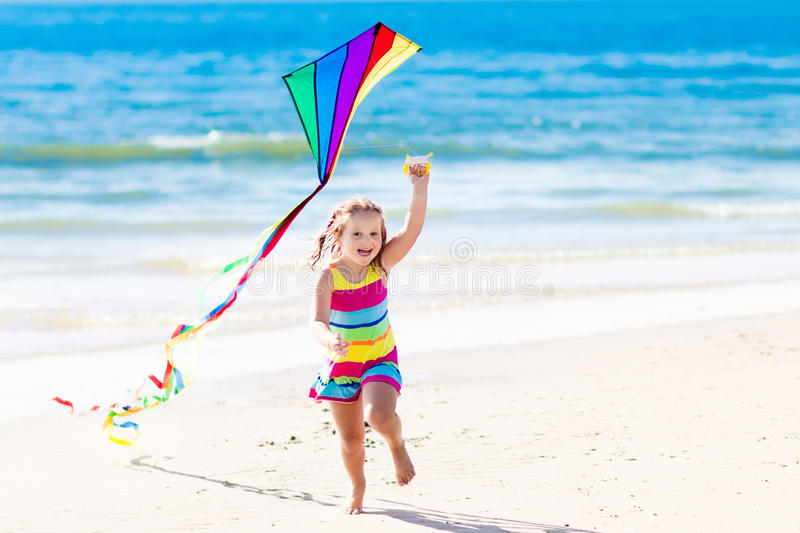 Child flying kite on tropical beach stock image