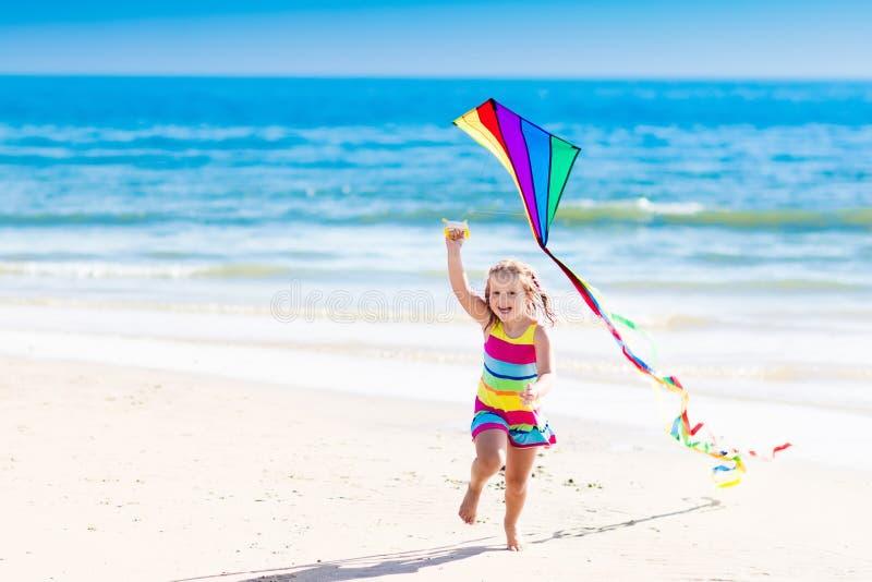 Child flying kite on tropical beach royalty free stock photos