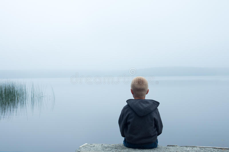 Child in foggy day. Sad child sitting alone by lake in a foggy day, back view stock photography