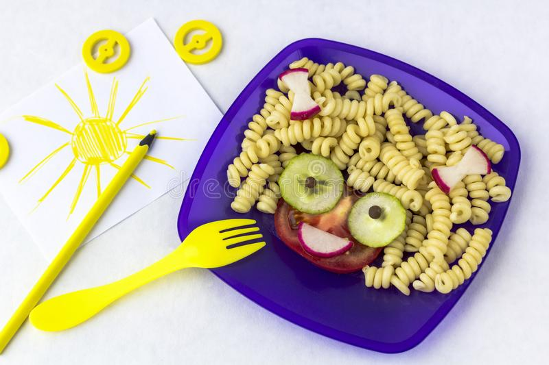 Child food. Funny food. Plate with pasta. With vegetables in the form of funny face. Children`s menu. Ð¡hildren`s lunch concept royalty free stock image