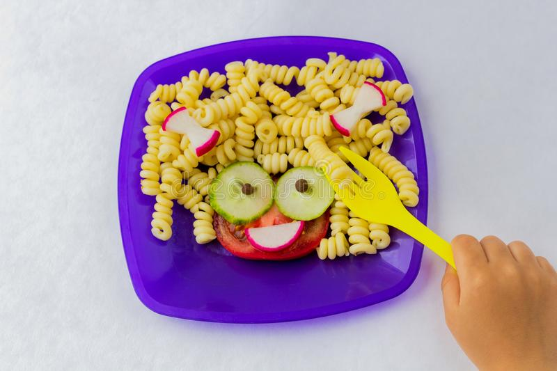 Child food. Funny food. Plate with pasta. With vegetables in the form of funny face. Children`s menu. Children`s lunch concept royalty free stock photo
