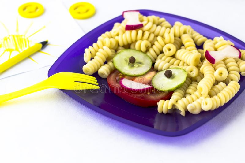Child food. Funny food. Plate with pasta. With vegetables in the form of funny face. Children`s menu. Children`s lunch concept stock photos