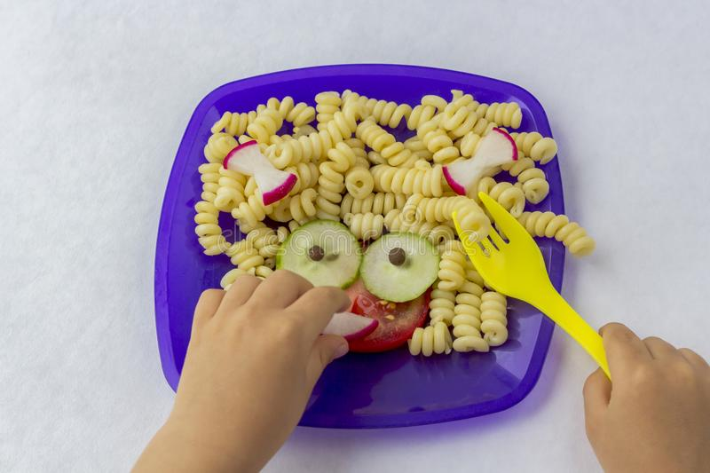 Child food. Funny food. Plate with pasta. With vegetables in the form of funny face . Children`s menu. Children`s lunch concept royalty free stock images