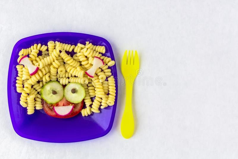 Child food. Funny food. Plate with pasta. With vegetables in the form of funny face with space for text. Children`s menu. Children`s lunch concept stock photos