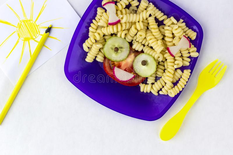 Child food. Funny food. Plate with pasta. With vegetables in the form of funny face with space for text. Children`s menu. Children`s lunch concept stock photo
