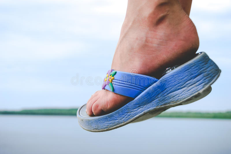 Child foot wearing flip-flops in air and landscape view. Landscape with water and sky royalty free stock photos