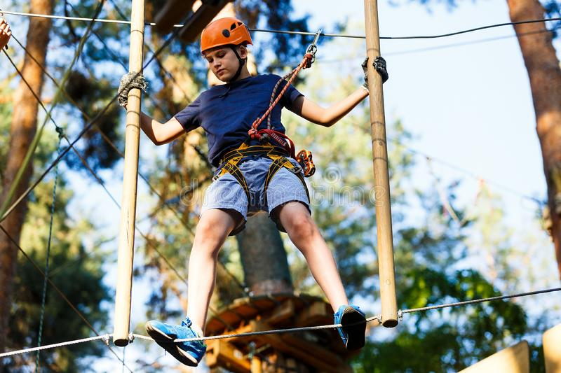 Child in forest adventure park. Kid in orange helmet and blue t shirt climbs on high rope trail. Agility skills and climbing. Outdoor amusement center for stock photography