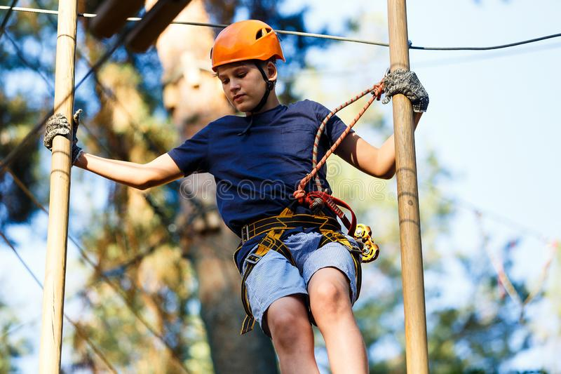 Child in forest adventure park. Kid in orange helmet and blue t shirt climbs on high rope trail. Agility skills. And climbing outdoor amusement center for stock image