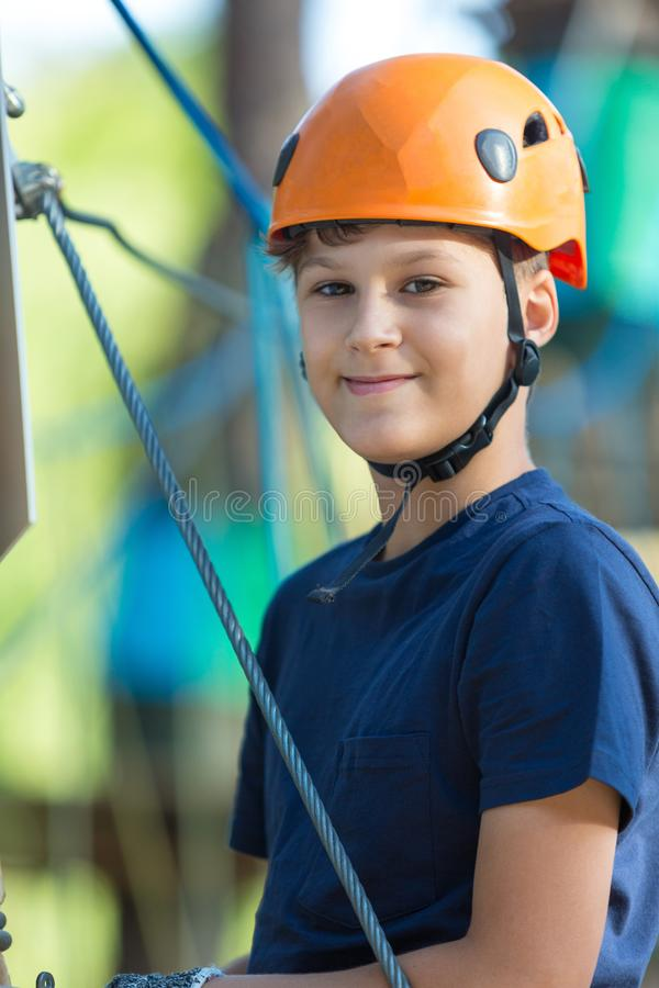 Child in forest adventure park. Kid in orange helmet and blue t shirt climbs on high rope trail. stock photography