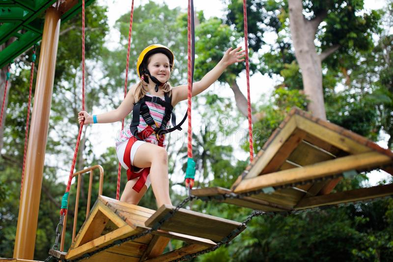 Child in forest adventure park. Kids climb on high rope trail. Agility and climbing outdoor amusement center for children. Little. Girl playing outdoors. School stock images