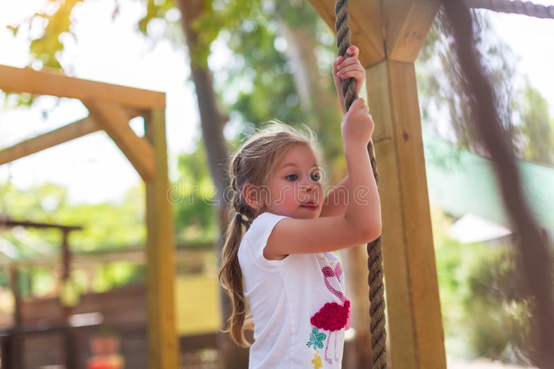 Child in forest adventure park. Kids climb on high rope trail. Agility and climbing outdoor amusement center for children. Little girl playing outdoors. School stock image