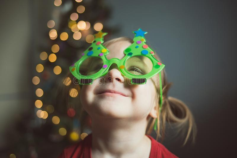 Child in funny glasses in the form of Christmas trees on the background of lights. girl looks up stock image