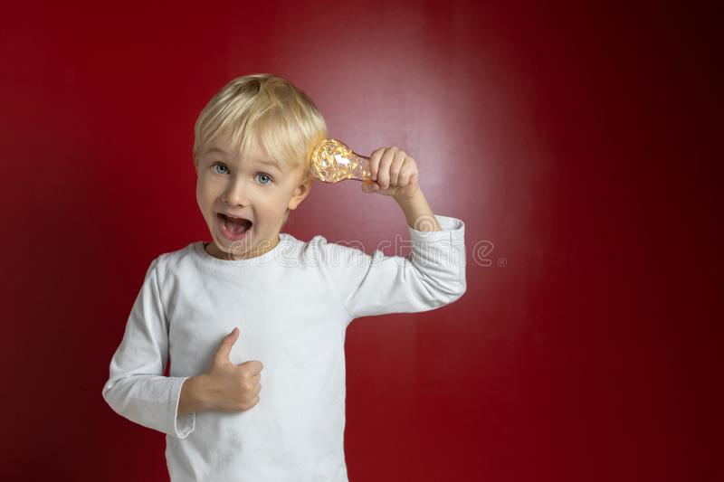 Child funny grimace with light bulb royalty free stock photography