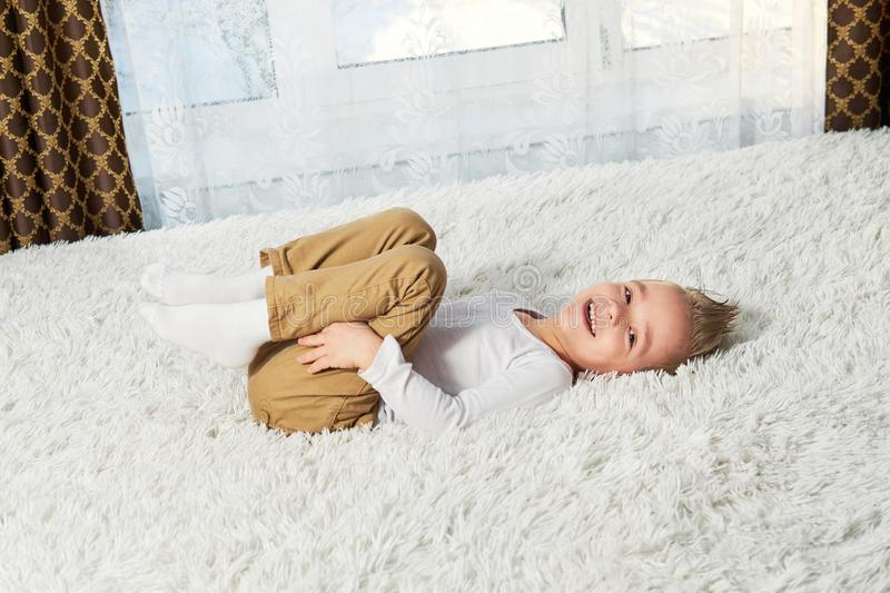 Child funny home. Happy boy blond lying on soft bedspread bed, top view. Little kid laughing while looking at camera. stock image