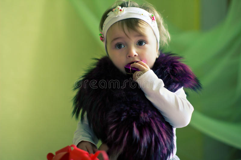 Child with fur on shoulders chews gift. Child with fur on shoulders chews little gift royalty free stock photography