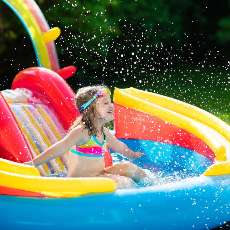 Child Playing In Inflatable Baby Pool Kids Swim Slide And Splash Colorful Garden Play Center Happy Little Girl Sliding Swimming With Water Toys On