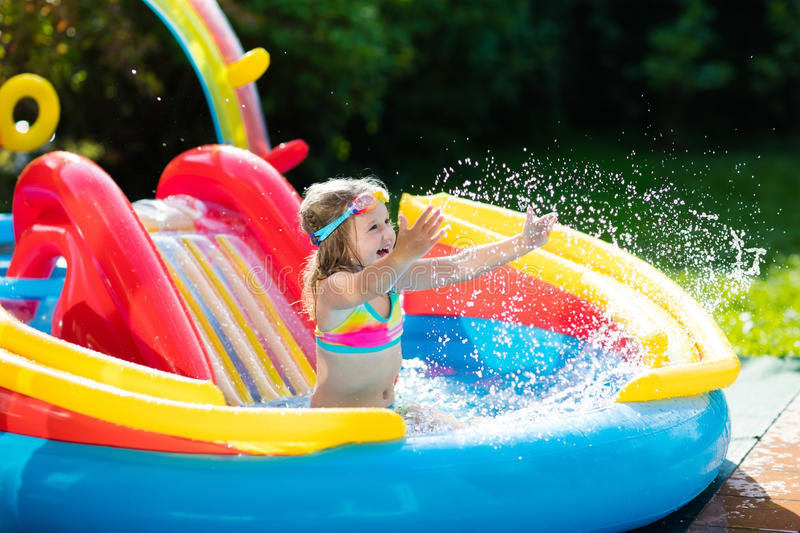 Download Child In Garden Swimming Pool With Slide Stock Photo