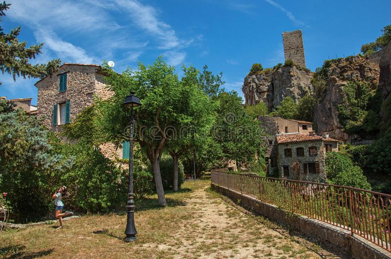 Child in a garden with trees, houses and cliff in Chateaudouble stock photo