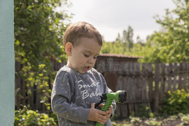 Child in the garden watering flowers royalty free stock images