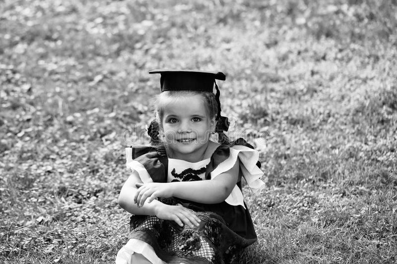 Child is a genius. The child is a child prodigy. Cute little girl with long hair in black graduation cap. Child is a genius. The child is a child prodigy. Cute stock photos