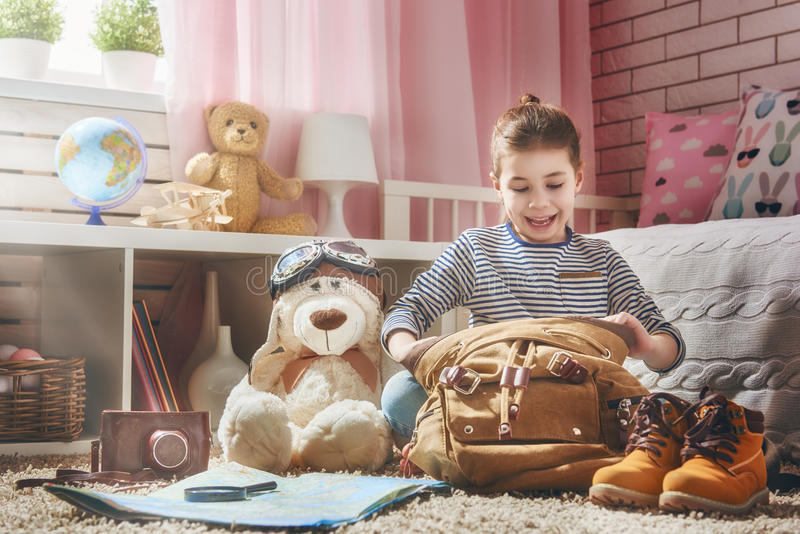 Child getting ready for journey. Happy child is getting ready for the journey. Girl is packing her bags and having fun in kids room at home stock images