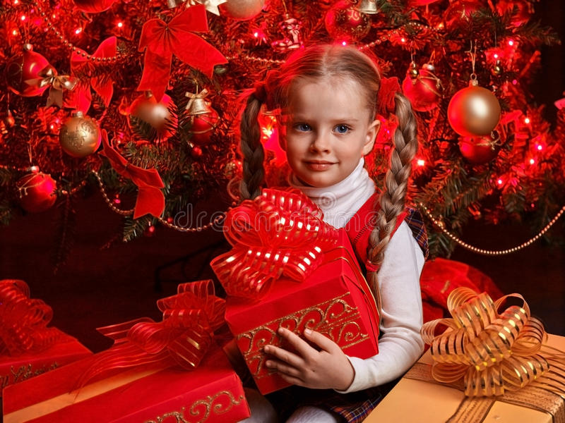 Child with gift box near Christmas tree. stock images