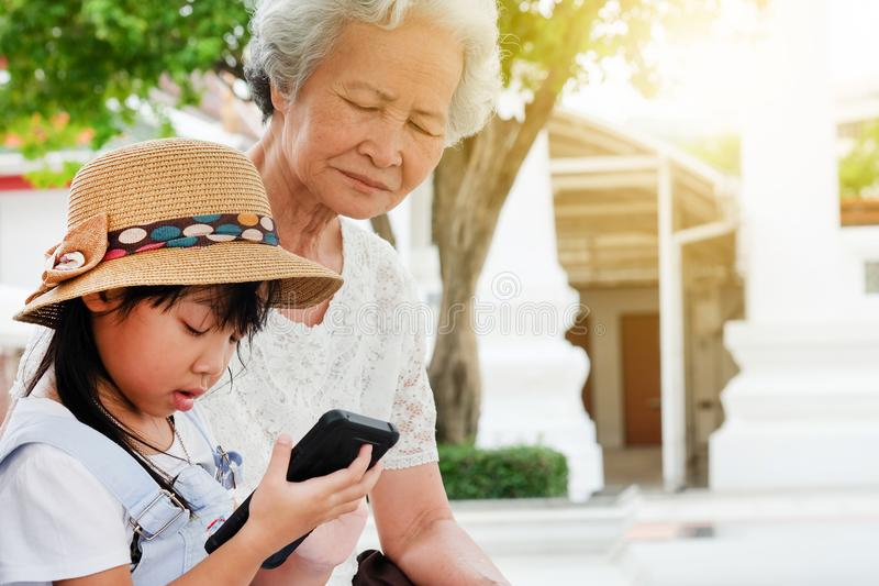 Child girl is addictive, have an elderly grandmother sit. Asian child girl is addictive, play mobile phone addicted to the game, have an elderly grandmother sit royalty free stock image