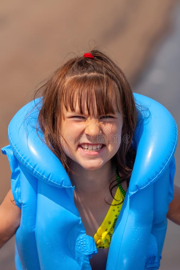 Child girl in a blue inflatable life jacket makes a grimace. royalty free stock photo