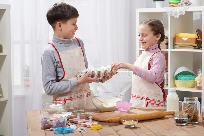 Child girl and boy cooking in home kitchen, hold eggs in the hands stock image