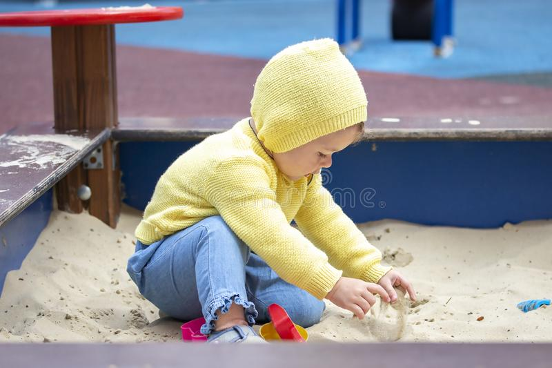 Child girl boy european playing with sand in a sandbox. Child baby one year old takes the sand with his hands touches on the stock photo