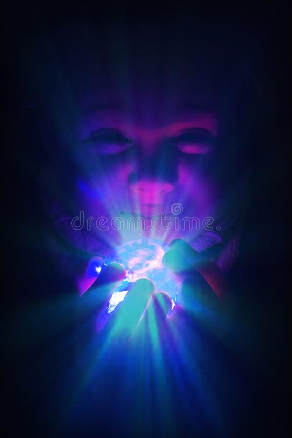 Child girl with a brilliant glass ball with flare an lights. Imagination and fantasy metaphor with empty copy space stock images