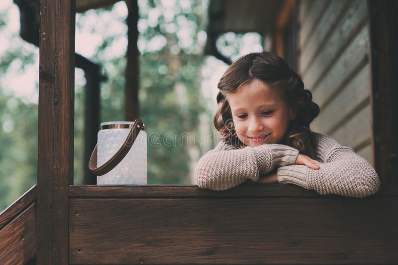Child girl with candle holder relaxing in evening at cozy country house. Kid spending summer vacation in log cabin in the woods stock photography