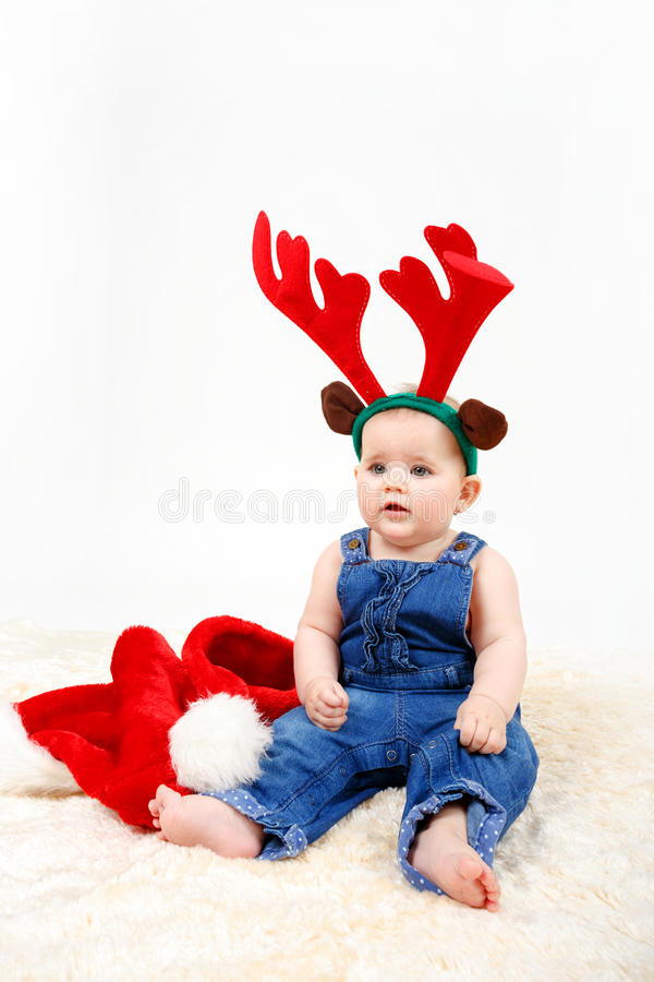 Child girl with Christmas santa hat and reindeer antlers. On white background royalty free stock photography