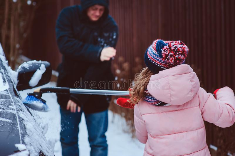 Child girl cleaning car from snow with dad after snow fall. In winter royalty free stock image