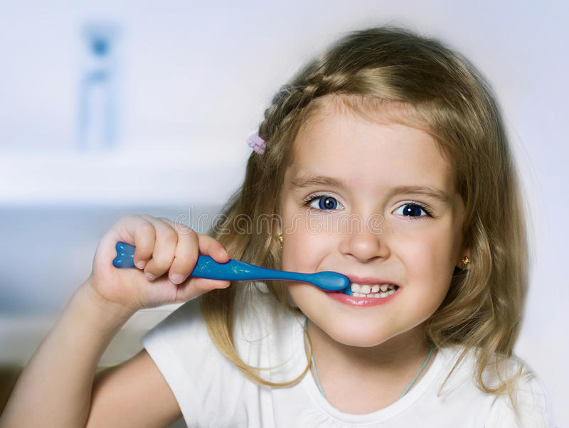 Child girl cleaning teeth with toothbrush. royalty free stock images