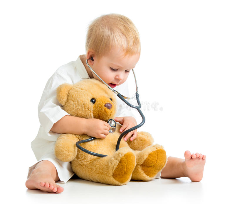 Child girl with clothes of doctor and teddy bear. Adorable girl with clothes of doctor on white stock photo