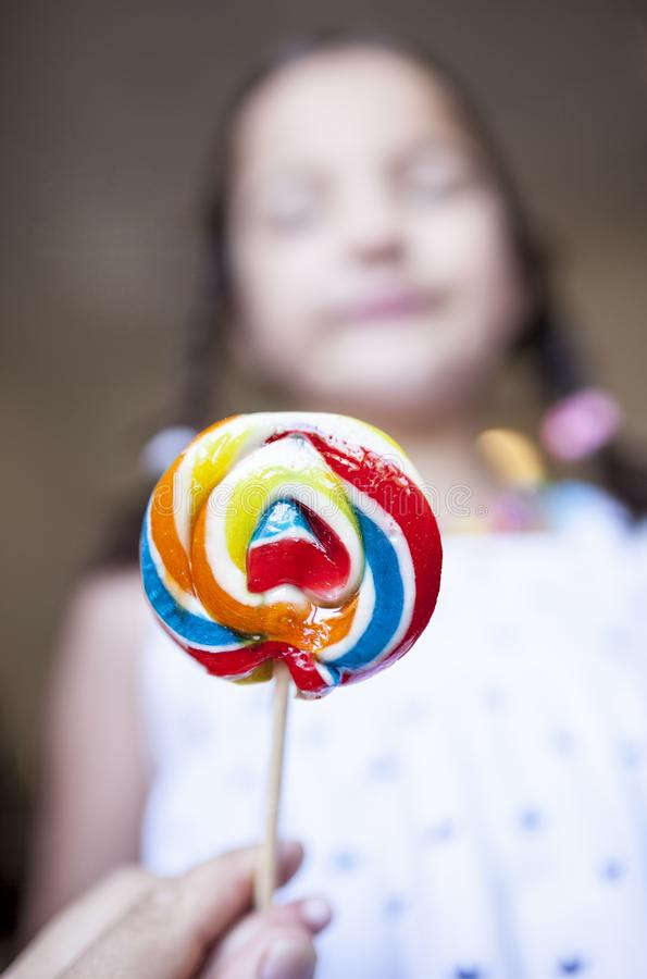 Child girl with colorful big lollipop. Selective focus. Unhealthy food for children concept royalty free stock image
