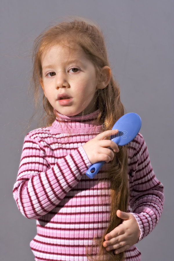 child girl with comb brushing