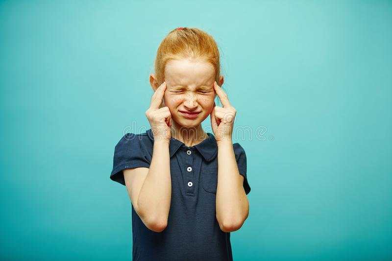 Child girl concentrated way thinks, thigtly closed eyes. stock photography
