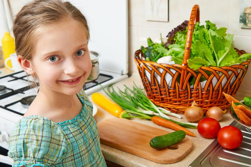 Child girl cooking in home kitchen. Basket of vegetables and fresh fruits in kitchen interior. Healthy food concept stock image